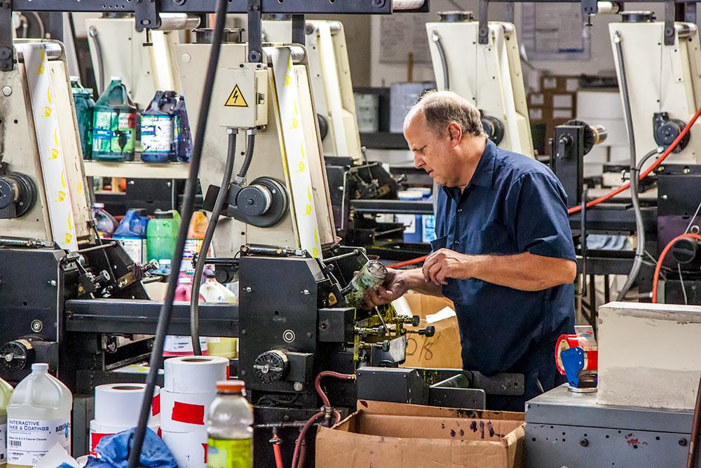 Man working on industrial printers